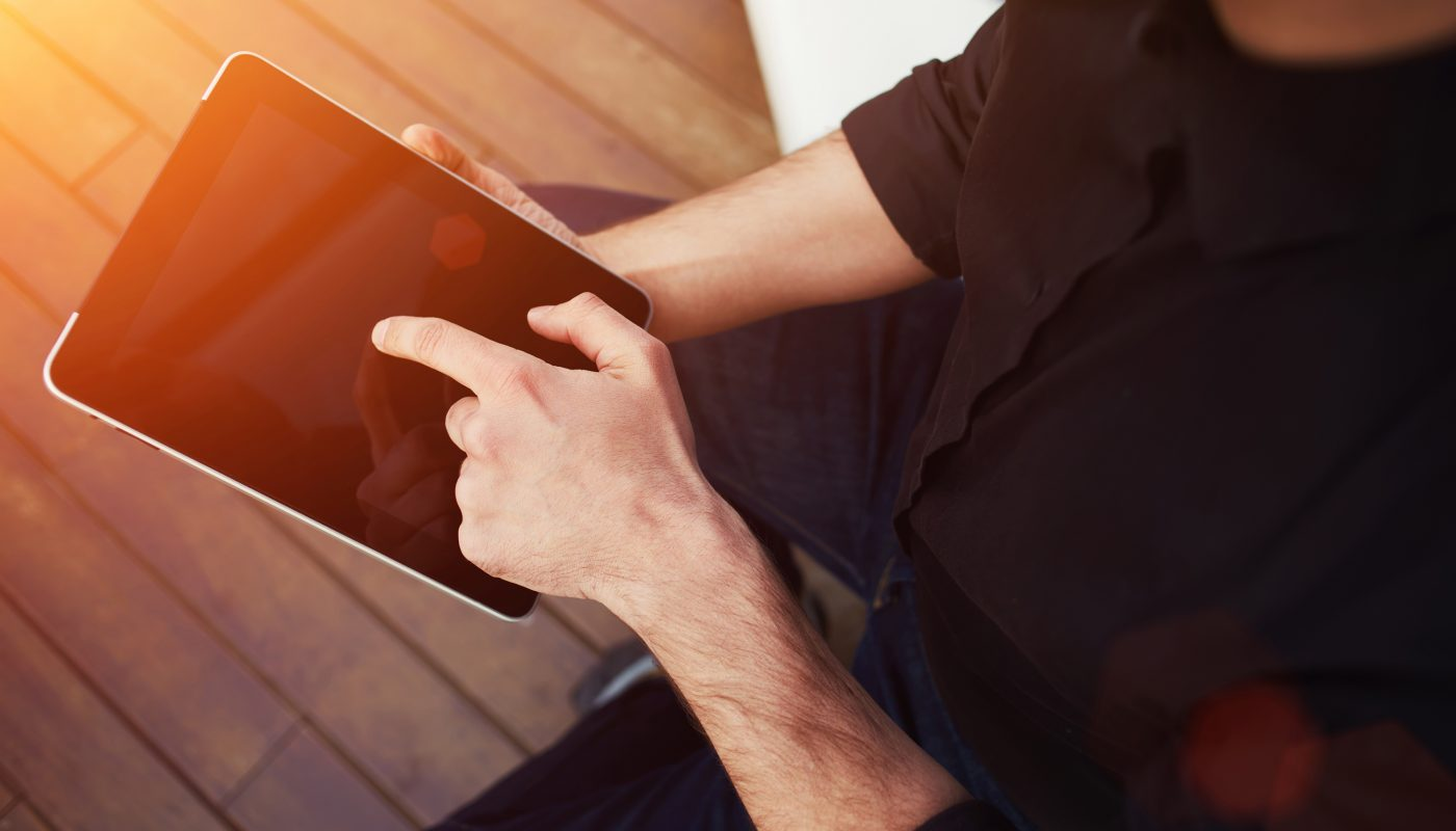 Close up to view young man's hands hold black tablet with blank empty screen, male hands holding touch screen tablet pc with blanc screen, flare sun light